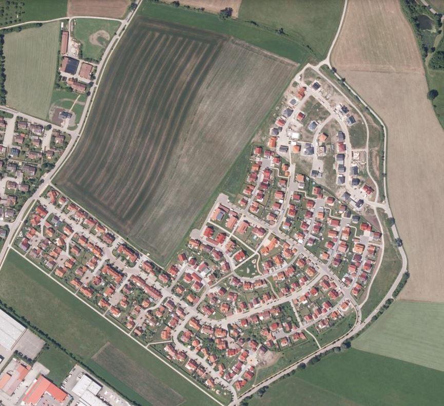 Ein Bauernhof (oben links) wird von Einzelhaussiedlungen eingekreist.